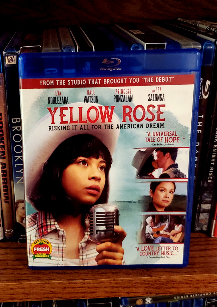 Photo of the Blu-ray case for Yellow Rose in front of the spines of other Blu-rays