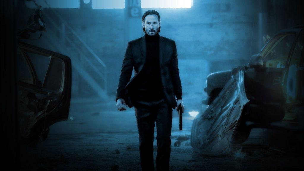 John Wick walks carrying a gun